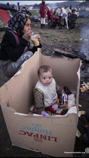 niño.refugiado.cartones.lloviendo